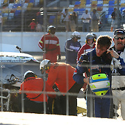 Racecar driver Parker Kligerman walks away from his Swan Energy Toyota after flipping onto its roof during a crash at the 56th Annual NASCAR Daytona 500 practice session at Daytona International Speedway on Wednesday, February 19, 2014 in Daytona Beach, Florida.  (AP Photo/Alex Menendez)