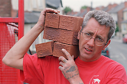 Portrait of builder carrying pile of bricks on shoulder,