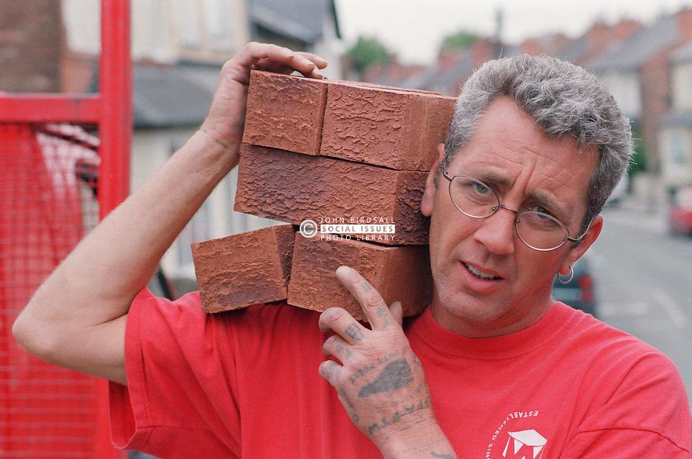 Portrait of builder carrying pile of bricks on shoulder,