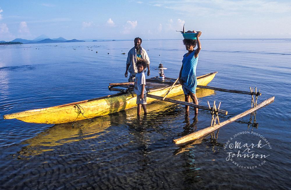 Family near outrigger canoe, New Britain Island, Papua New Guinea