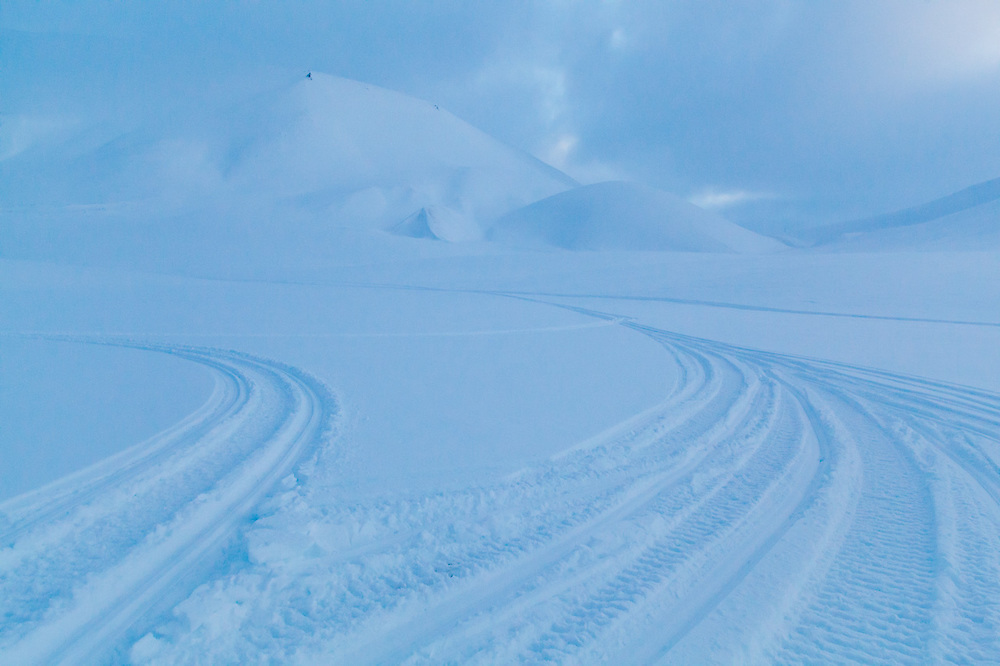 Snowmobile tracks in the snow left by UNIS students driving their snowmobiles during a training course in Adventdalen, Svalbard.