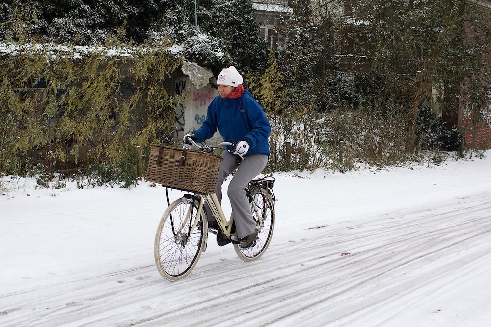 Een vrouw fietst op de Amsterdamseweg in Arnhem door de sneeuw.<br /> <br /> A woman is cycling at the Amsterdamseweg in Arnhem in the snow.