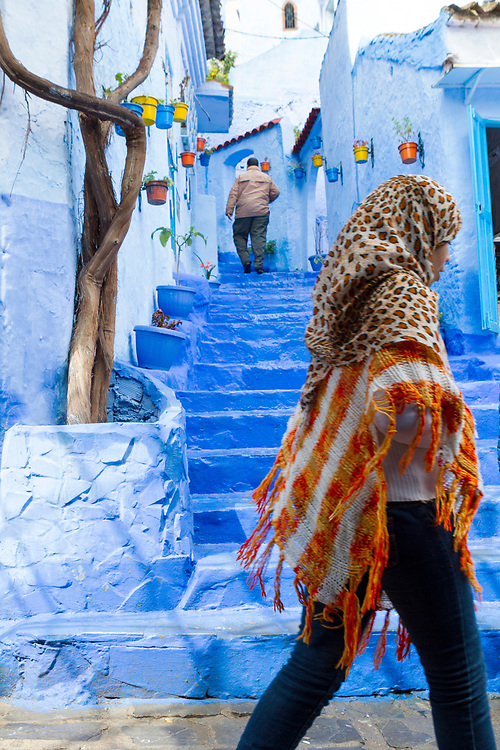 CHEFCHAOUEN, MOROCCO - 29th MARCH 2014 - Locals to Chefchaouen walk through a colourful street and steps lined with decorative flower and plant pots, Chefchaouen - the blue city - Rif Mountains, Northern Morocco.