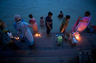 A group of women use oil lamps to light their way as they take their morning bath in the Ganges River