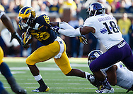 Oct 10, 2015; Ann Arbor, MI, USA; Michigan Wolverines wide receiver Jehu Chesson (86) breaks a tackle by Northwestern Wildcats linebacker Nate Hall (32) in the second quarter at Michigan Stadium. Mandatory Credit: Rick Osentoski-USA TODAY Sports