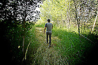 Bill Buley walks about of a forested area and into a clearing Friday, July 29, 2011 along the shoreline of a marsh near Cataldo, Idaho.