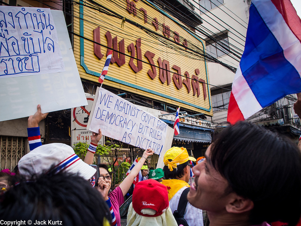 05 JANUARY 2014 - BANGKOK, THAILAND:  Anti-government protestors carrying signs, some in English, walk through Bangkok. Suthep Thaugsuband, leader of the anti-government protests in Bangkok, led the protestors on a march through the Chinatown district of Bangkok. Tens of thousands of people waving Thai flags and blowing whistles gridlocked what was already one of the most congested parts of the city. The march was intended to be a warm up to their plan by protestors to completely shut down Bangkok starting Jan. 13.    PHOTO BY JACK KURTZ