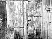 Detail of the wall of an old corrugated tin shack in the Arizona desert with a wonderful assortment of shiny and scratched metal textures. Black and white abstract fine art photography.