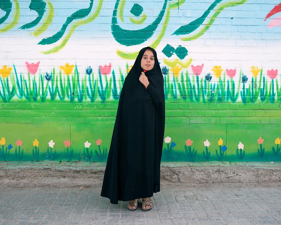 Portrait of a little girl in black chador