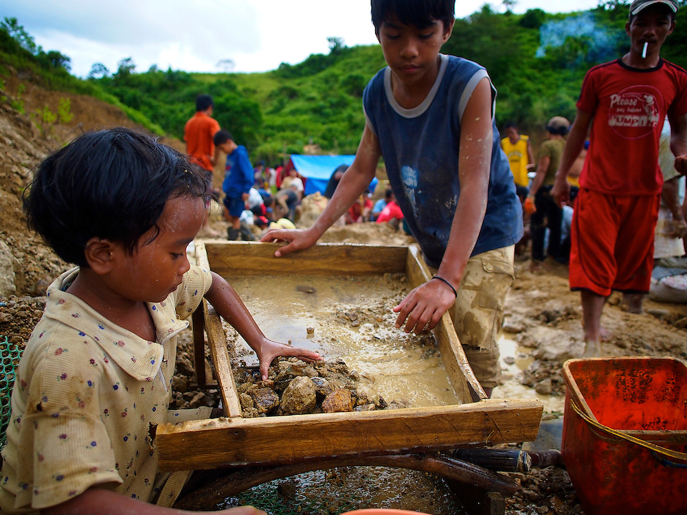 Children work alongside adults at the Panique mining area about 10 kilometers outside the town of Aroroy on the Island of Masbate.  Masbate is about 350 miles south of the Philippine capital of Manila.  The land is owned by CGA Mining Limited, a large-scale mining company based in Australia...CGA allows small-scale miners to informally work property they own.  On this day, miners working a small-scale operation for four months were told they had to leave the shafts they had dug to make way for heavy equipment and bull dozers who were filling in the area to built an access road.  ..Miners, families and children work to dig ore and pan the stream at the top of the mine shafts.  Young teens were working inside he 30-foot-pits with hammers and picks to fill plastic flour sacks with gold ore.  ..CGA company guards and local police ordered the eviction and check the shafts to make sure all miners are gone as a bulldozer moves in to cover the pits.  ..A woman is the last to leave and glances a the machine as she hurrays away with her belongings...On a hillside, a four-year-old boy cries as he carries a small sack of ore to a ridge above the mining area...Story Summary:.Small-scale gold mining in the Philippines uses mercury and cyanide to extract elemental gold from ore extracted from mines and pits dug by hand.  Very young children, some as young as four, are put to work at less dangerous but still rigorous tasks in the gold mining areas.  These include panning in streams or rivers and hauling ore sacks that can weigh up to 60 pounds.  Children often play near mechanized equipment and highly toxic mercury and cyanide.  These chemicals, used to help extract elemental gold from ore, are leached into nearby watersheds where fish and other marine life, mainstays of the Philippine diet, are poisoned.  The high price of gold and the poor economy in many developing countries has led to an increase in small-scale gold mining throughout the world.