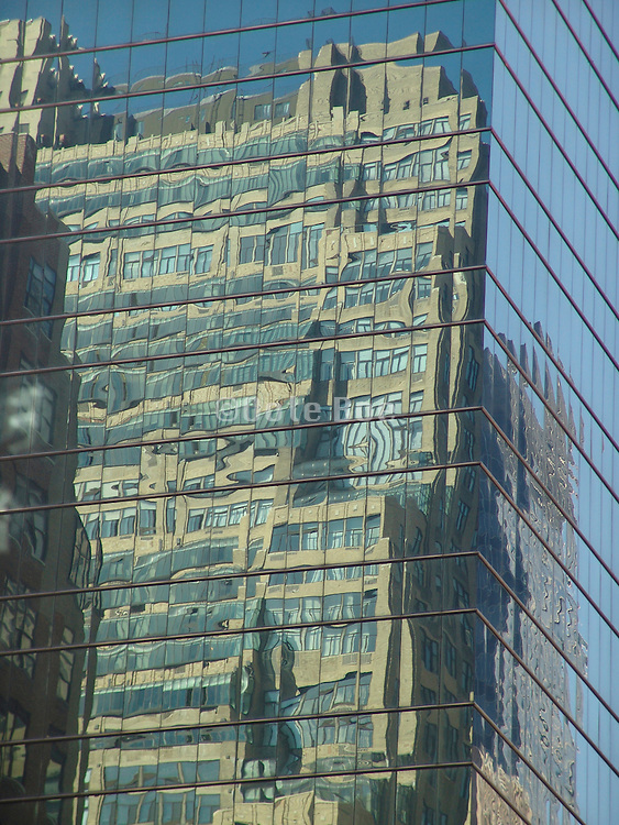 A residential building reflecting in a large office high rise.