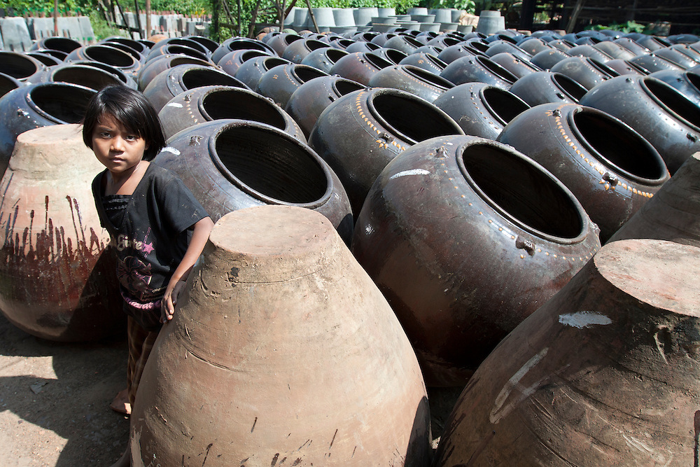 A girl in the middle of clay vases in pottery village of Twante near Yangon in Myanmar.