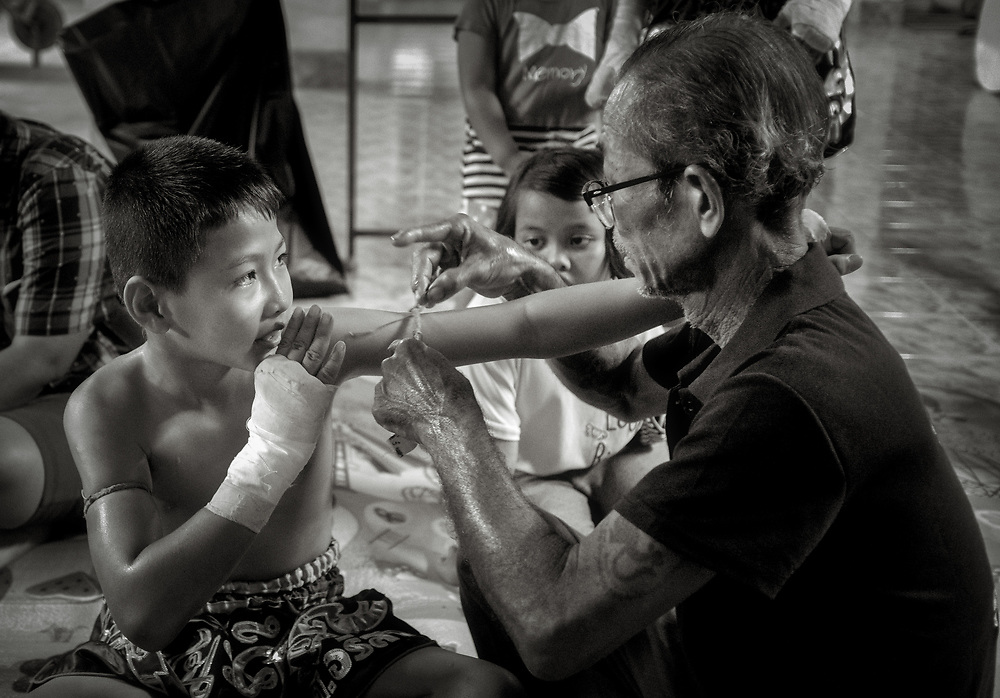 A young Muay Thai boxer has his prajioud (arm band) put on by his kru (coach) before a boxing match at a festival in Nakhon Nayok Thailand.