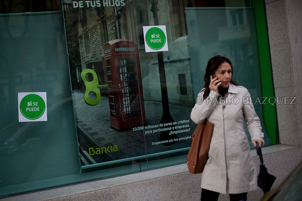 A woman walk outside a bankia's bank office after anti-eviction activists took part in a 'escrache' outside the house of Popular Party Deputy Mari Luz Prieto, on April 4, 2013 in Madrid, Spain. Sticker reads 'Yes we can'. The Mortgage Holders Platform (PAH) and other anti evictions organizations are organizing 'escraches' for several weeks under the slogan 'There are lifes at risk' to claim the vote for a Popular Legislative Initiative (ILP) to stop evictions, regulate dation in payment and social rent outside Popular Party deputies' houses and offices..'Escraches' are form of peaceful public protest that was used in Argentine in 1995 to point to pardoned genocides of Argentenia's Dictatorship within their neighborhoods.