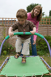 Nanny and little boy playing on the trampoline in the garden,