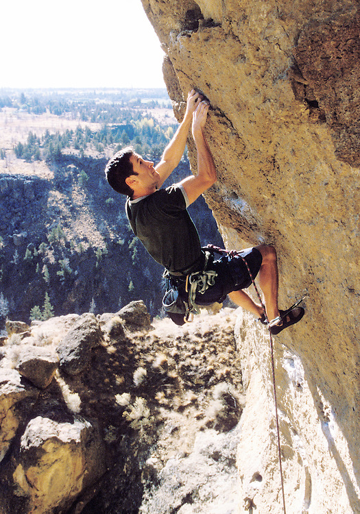 A man rock climbing on an overhanging cliff wall at Smith Rock State Park, Oregon, USA.