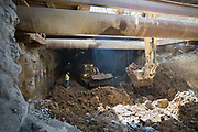 Coordinated efforts between bulldozers, a surface-level excavator, and dump trucks allow for excavation of the station box and north concourse under Stockton Street.