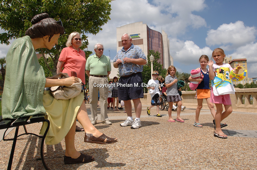 Retirees and children look at a lifelike sculpture seated on a park bench around Lake Mirror Park in downtown Lakeland, Florida.  The sculpture is one of many sculptures adorning the park.