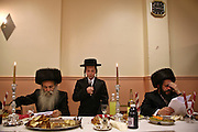 A 13 year-old Orthodox Jewish boy recites the Torah during Bar Mitzvah.  His father and grandfather listen closely to make sure he doesn't make any mistakes. The Bar Mitzvah signals the coming of age for a young Jewish boy, they become responsible to observe the commandments of the Torah. It coincides with physical puberty and they begin to participate in all areas of Jewish life. A Bar mitzvah ceremony is a big occasion, the young boy reads a section from the Torah to his family and friends and a mitzvah meal is consumed.