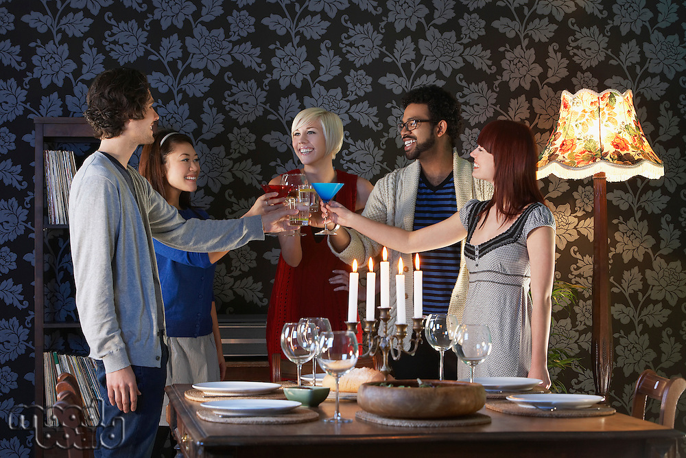 Group of people toasting standing by dining table