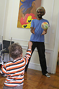 11 October 2013. Manhattan, New York. 666 162nd St. Gio Livingston plays catch at home with his one-year-old son, Julius. 10/11/13. Photograph by Nathan Place/NYCity Photo Wire