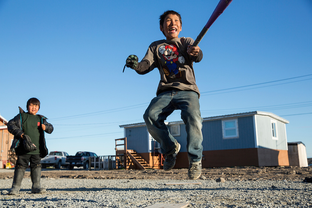 Canada, Nunavut Territory, Whale Cove, Young boy leaps for joy after hit during pickup baseball game in Inuit hunting village along Hudson Bay