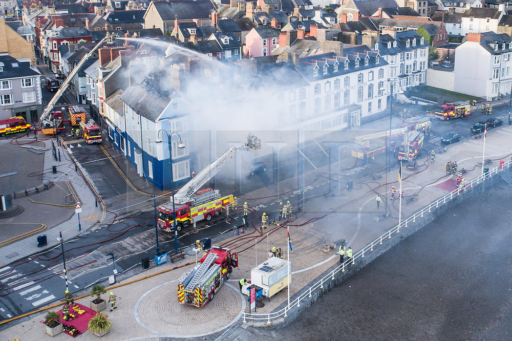 ©Licensed to London News Pictures. Aberystwyth Wales UK, Wednesday 25 July 2018. A major fire has severely damaged two adjoining hotels so Aberystwyth seafront. The Belle Vue hotel and the Belgrade Hotel caught fire at around 2am this morning, Fire engines from all over Mid and west wales have been in attendance throughout the night. There are no reports of casualties, and all the guests have been transferred to other accommodation . Much of the centre of the town has been cordoned off for safety reasons. photo credit : Keith Morris / LNP