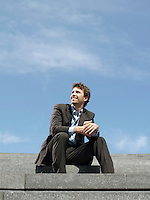 Businessman sitting on steps outdoors low angle view