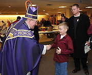 Green Bay Bishop David Ricken shakes hands with Bryan Geenen, 9, son of Bob and Kate Geenen, following Mass Feb. 28 at St. Pius X Church in Appleton. Bishop Ricken celebrated the closing Mass at the Esto Vir Men's Conference, which attracted about 650 Catholic men. (Sam Lucero photo)