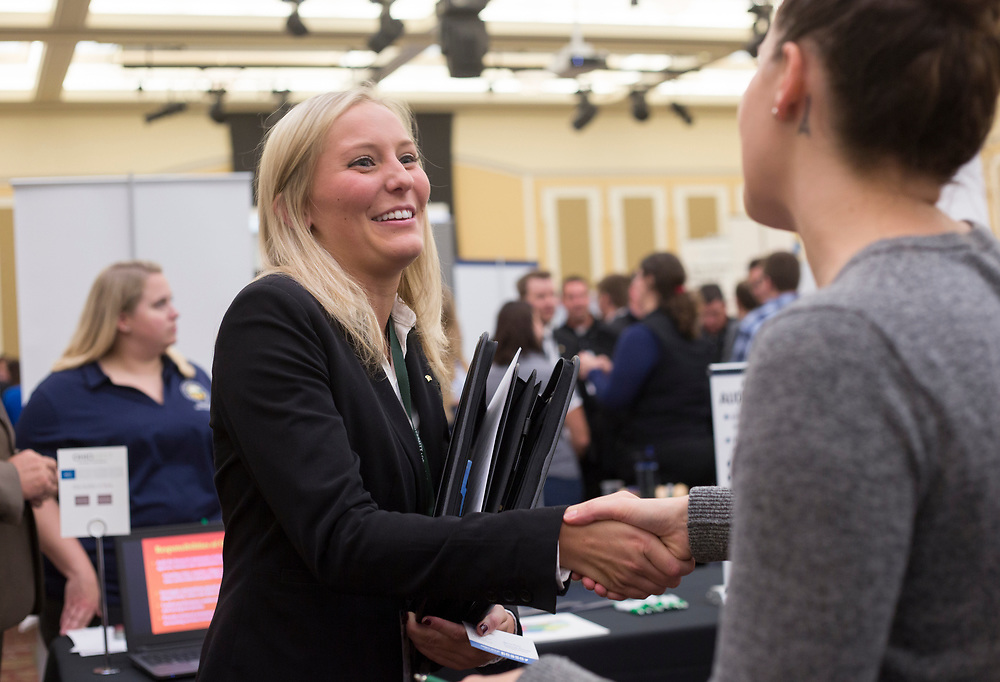 Kaitlyn Runner, left, shakes hands with Becca Perna, a corporative recruiter for Reynolds and Reynolds, at the College of Business Conference on September 7, 2017.
