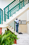 Miami Modern stair railings, mailboxes and a postal worker at a small apartment building in Miami Beach