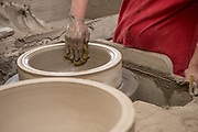 Employee Russell Hall forms a large pot by hand  at Burley Clay in Roseville. Photo by Ben Siegel