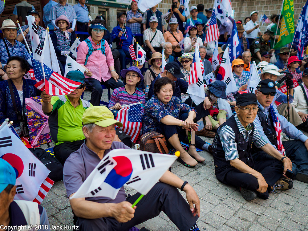 16 JUNE 2018 - SEOUL, SOUTH KOREA: South Koreans with South Korean and American flags during a protest against South Korean President Moon Jae-in. Most of the protesters support jailed former President Park Geun-hye. President Moon Jae-in was elected in 2017 after Park was impeached, tried and convicted on corruption charges. The protesters allege that Moon is too soft on North Korea and can't be trusted to negotiate with North Korean leader Kim Jong-un. They support US President Donald Trump's efforts to negotiate with the North Korean strongman.   PHOTO BY JACK KURTZ