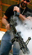 A man cleans a hot gun with oil right after a firing round during the Knob Creek Machine Gun Shoot near West Point, Kentucky April 10, 2005. Thousands of machine gun and military hardware enthusiasts attended the event held each year over weekends in the spring and fall.