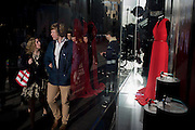 Passers-by and London Fashion Week red dress in central London window