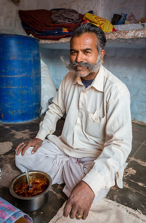 A Bishnoi man hosts a lunch in a homestay. Bishnoi cuisine is strictly vegetarian, and uses sprouts from the kej'ri tree, which is a sacred tree to the tribe.