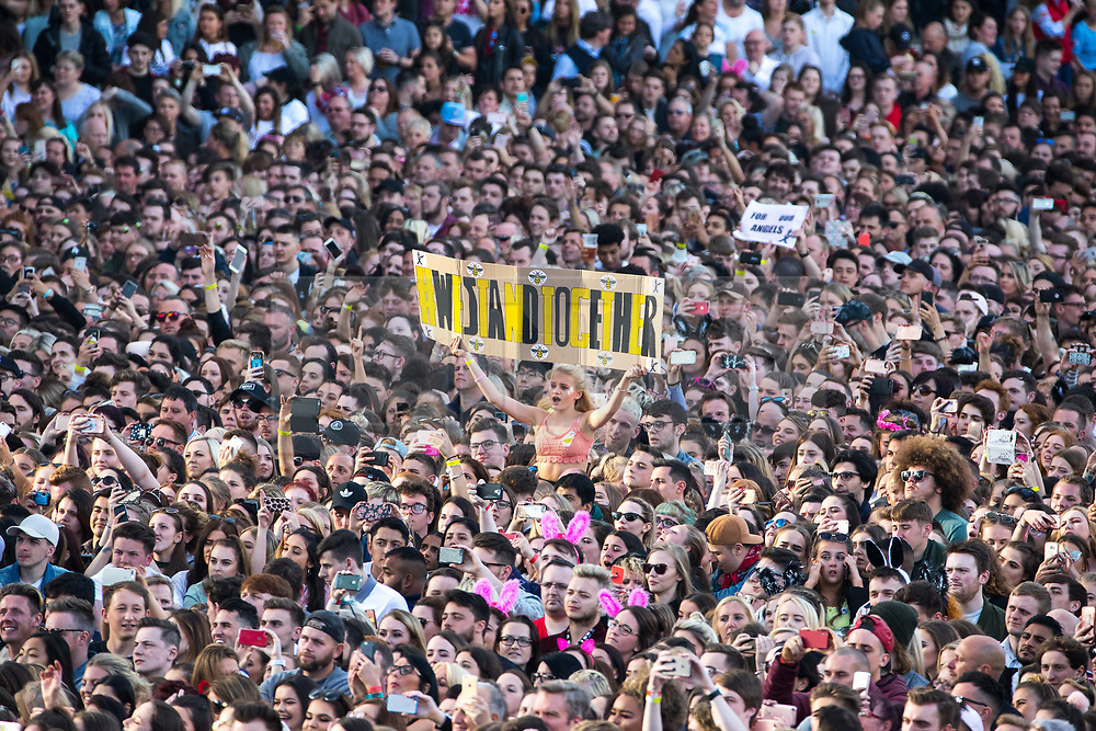"© Licensed to London News Pictures . 04/06/2017 . Manchester , UK . A woman holds up a "" We Stand Together "" banner with Manchester worker bees stuck around the outside . The One Love Manchester benefit concert for victims of the Manchester Arena terrorist attack , at the Emirates Old Trafford Cricket Stadium . Ariana Grande, Justin Bieber, Coldplay, Katy Perry, Miley Cyrus, Pharrell Williams, Usher, Take That, Robbie Williams, Black Eyed Peas and Niall Horan are amongst the performers. Photo credit : Joel Goodman/LNP"