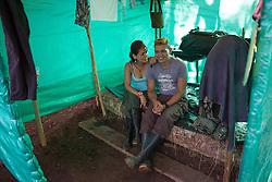 El Diamante, Meta, Colombia - 15.09.2016        <br /> <br /> A guerilla couple sitting on a bed inside their booth. Guerilla camp during the 10th conference of the marxist FARC-EP in El Diamante, a Guerilla controlled area in the Colombian district Meta. Few days ahead of the peace contract passing after 52 years of war with the Colombian Governement wants the FARC decide on the 7-days long conferce their transformation into a unarmed political organization. <br /> <br /> Ein Guerilla Paerchen sitz auf dem Bett in ihrem kleinen Unterschlupf. Guerilla-Camps zur zehnten Konferenz der marxistischen FARC-EP in El Diamante, einem von der Guerilla kontrollierten Gebiet im kolumbianischen Region Meta. Wenige Tage vor der geplanten Verabschiedung eines Friedensvertrags nach 52 Jahren Krieg mit der kolumbianischen Regierung will die FARC auf ihrer sieben taegigen Konferenz die Umwandlung in eine unbewaffneten politischen Organisation beschlieflen. <br />  <br /> Photo: Bjoern Kietzmann