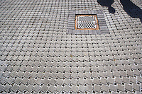 Two peoples shadows on a permeable surface roadway with storm drain.