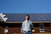 University Park, Maryland - May 04, 2015: David Brosch, President of the University Park Community Solar, LLC, stands in front of a 22 kilowatt solar electric array atop the roof of the University Park Church of the Brethren in University Park, Maryland Monday May 4th, 2015. The solar panels on top of the church produces an estimated 25% more energy than the church needs per year. Members of the LLC who helped pay for the solar panels receive dividends based on the money they invested, but no energy. <br /> <br /> CREDIT: Matt Roth