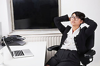 Young businesswoman resting on chair in front of laptop in office