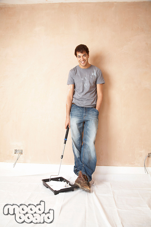 Man holding paint roller in paint tray in unrenovated room portrait