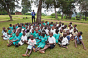 At Nyamiyaga primary school the Bwindi Community Hospital run health outreach programs. Reverend Sam, Head of Community Health, works on a sight test game with the children. As part of the outreach programme they cover 32 primary schools and 5 secondary schools in the region as well as many communities. The main Bwindi Community Hospital is in Buhoma village on the edge of the Bwindi Impenetrable Forest in Western Uganda. It serves around 250,000 people from the surrounding area.
