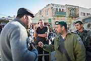 Palestinian human rights defender Issa Amro speaks to an Israel Border Police officer while a settler named Ofer Ohana films the exchange on his phone. Responding to an order from Ohana, the Border Police officer stops Amro and a delegation from Breaking the Silence from passing through the checkpoint, disrupting the tour.