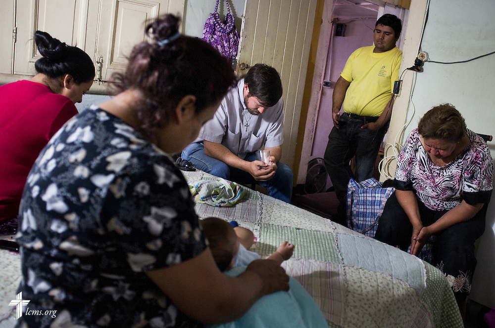 The Rev. Cristian E. Rautenberg, president of the Confessional Lutheran Church of Chile, prays with a family during a home visit on Wednesday, April 23, 2014, in Iquique, Chile. The city was damaged from a magnitude 8.2 earthquake on April 1, 2014 approximately 95km northwest of Iquique. The earthquake condemned several thousand homes and severely damaged more than ten thousand others. LCMS Communications/Erik M. Lunsford