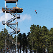Charlotte, NC -  A thrill seeker zip lines down one of the USNWC's newest additions. (Logan Cyrus for Charlotte magazine)