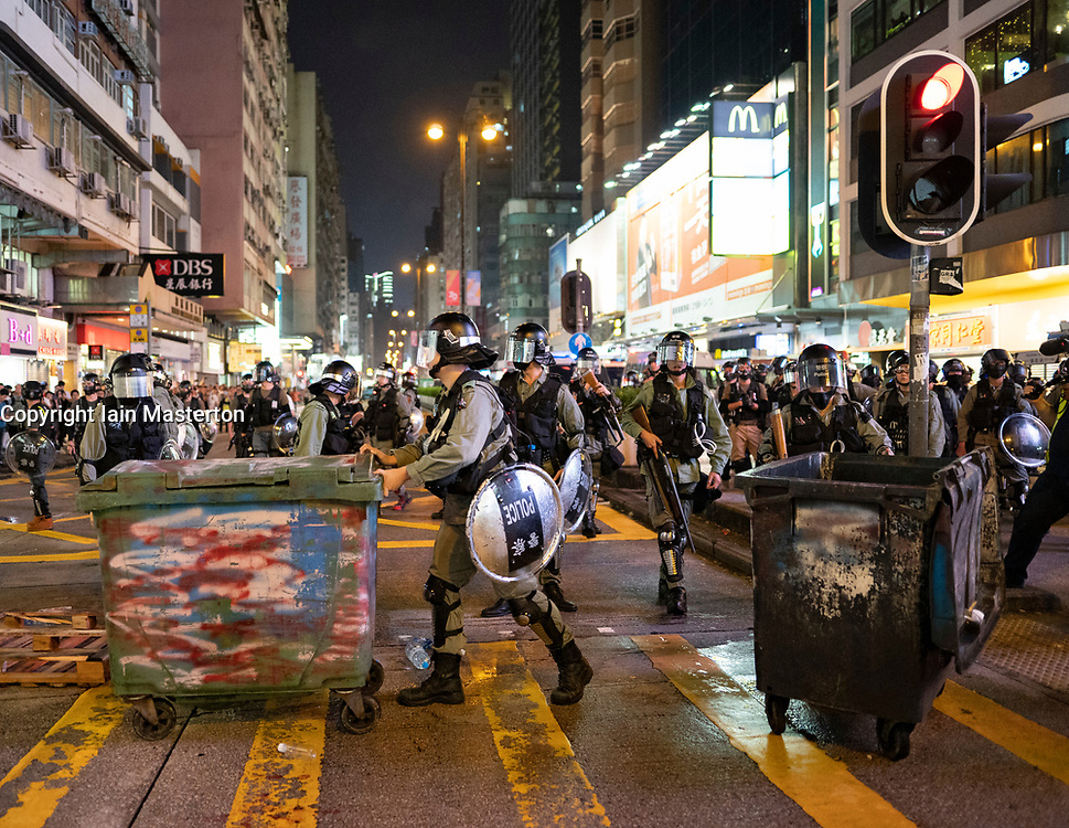 Hong Kong, China. 13th October 2019. Woman suspected of being pro-Beijing is assaulted by pro-democracy protestors in Mongkok district in Kowloon on Sunday evening. This incident was one of several throughout Hong Kong on Sunday which saw acts of vandalism carried out by a minority in the pro-democracy movement. Pic Police clear barricade on main thoroughfare Nathan Road.  Iain Masterton/Alamy Live News.