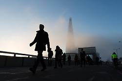 © Licensed to London News Pictures. 22/12/2016. LONDON, UK.  Commuters walk across London Bridge in front of the London Shard as fog begins to lift and the blue sky and sunshine arrive. After a cold and foggy start to the day, London is now seeing bright and sunny weather today. Photo credit: Vickie Flores/LNP
