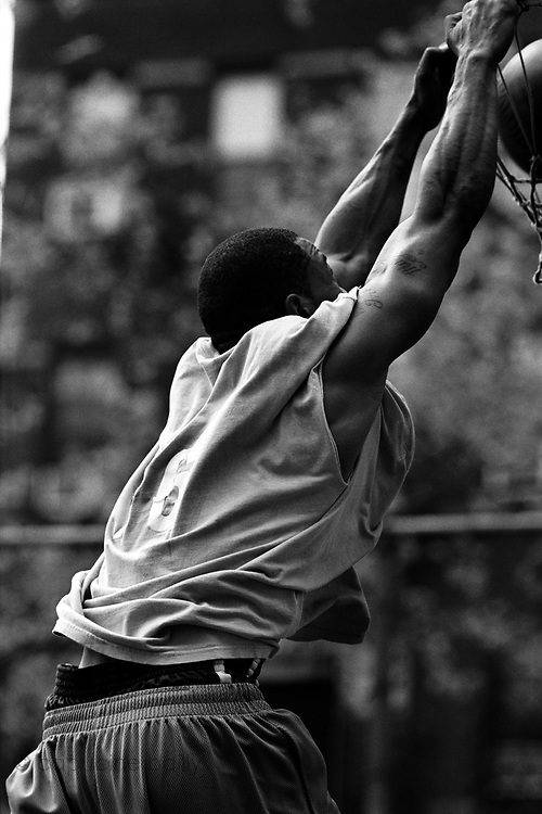 May 2nd 2003. New York, New York. United States..Located in the heart of Greenwich Village, the West 4th Street basketball Court, known as ?The Cage?, offers no seating but attracts the best players and a lot of spectators as soon as spring is around the corner..Half the size of a regular basketball court, it creates a fast, high level of play. The more people watch, the more intense the games get. « The Cage » is a free show. Amazing actions, insults and fights sometimes, create tensions among and inside the teams. The strongest impose their rules. Charisma is present..?The Cage? is a microcosm. It?s a meeting point for the African American street culture of New York. Often originally from Jamaica or other islands of the Caribbean, they hang out, talk, joke, laugh, comment the game, smoke? Whether they play or not, they?re here, inside ?The Cage?. Everybody knows everybody, they all greet each other, they shake hands and hug: ?Yo, whasup man??.