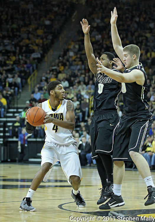 December 28, 2011: Iowa Hawkeyes guard/forward Roy Devyn Marble (4) tries to avoid Purdue Boilermakers guard Terone Johnson (0) and Purdue Boilermakers forward Travis Carroll (50) during the NCAA basketball game between the Purdue Boilermakers and the Iowa Hawkeyes at Carver-Hawkeye Arena in Iowa City, Iowa on Wednesday, December 28, 2011. Purdue defeated Iowa 79-76.